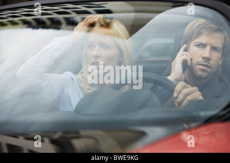 Business people sitting in electric car - Stock Photo