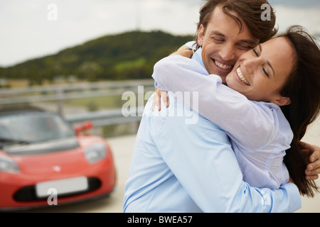Couple hugging in front of electric car - Stock Photo