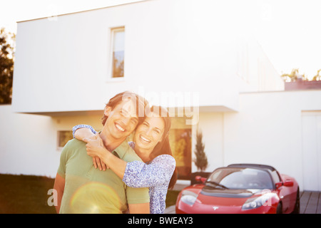 Couple posing in front of house and car - Stock Photo
