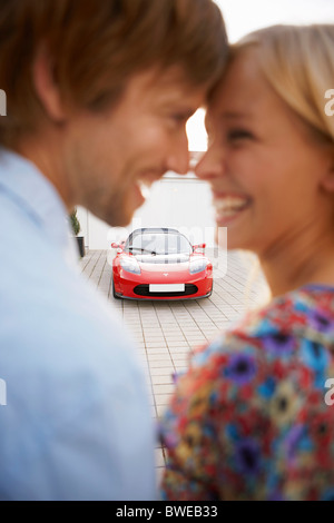 Couple close, electric car in background - Stock Photo