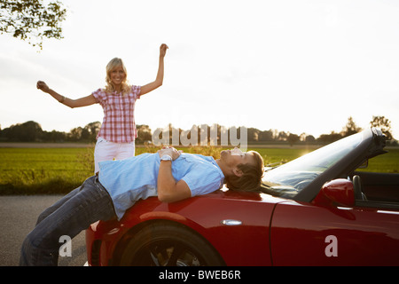 Couple relaxing in nature around a car - Stock Photo