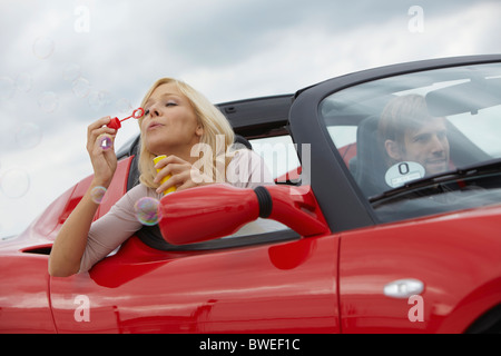 Couple in electric car, blowing bubbles - Stock Photo