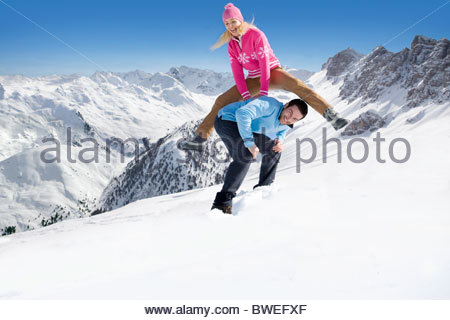 Laughing woman leap frogging over husband in snow - Stockfoto