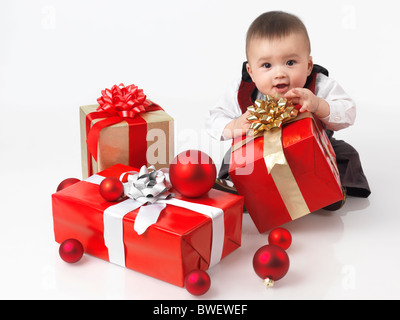 Happy six month old baby boy opening Christmas presents. Isolated on white background. - Stock Photo