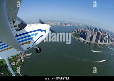 A light plane Cessna 172 flying over Lower Manhattan and Hudson river, New York city, USA - Stock Photo
