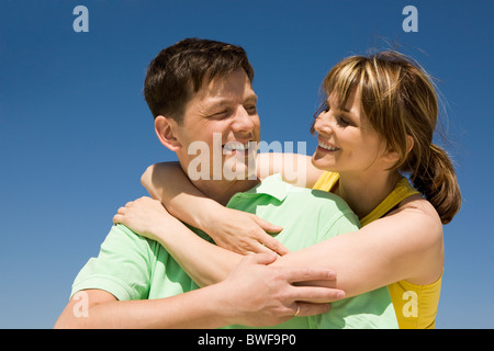 Photo of happy woman embracing her husband against bright blue sky - Stock Photo