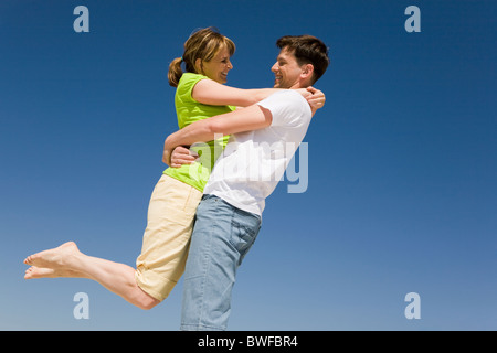 Photo of happy man holding his wife against bright blue sky - Stock Photo
