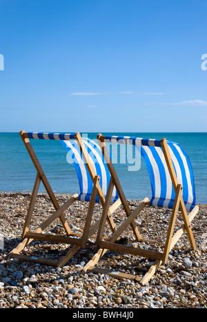 England, West Sussex, Bognor Regis, Two blue and white deck chairs on the shingle pebble beach looking out to sea. - Stock Photo
