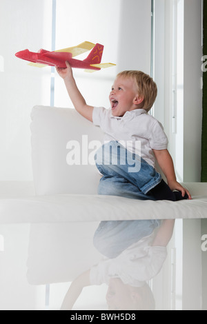 Young boy playing with toy plane - Stock Photo