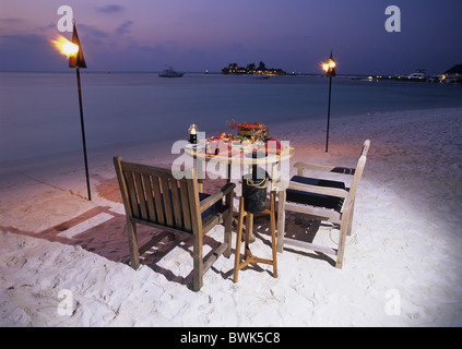 Maldives Asia Indian ocean island isle Kuda Huraa beach seashore food table desk chairs torches romantica - Stockfoto