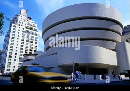 Taxi speeding past the Guggenheim Museum, New York City, New York, USA. - Stock Photo