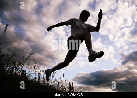 Photo of silhouette of jumping sportsman on a sky background - Stock Photo