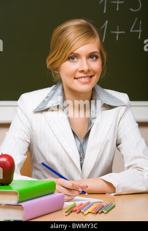 Portrait of young teacher checking up copybook with books near by and looking at camera with smile - Stock Photo