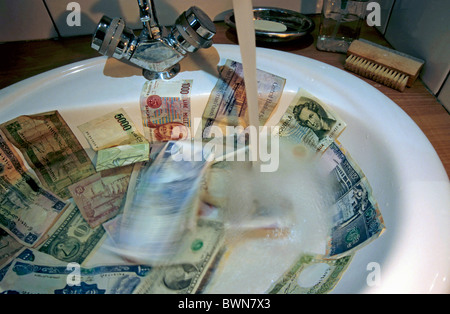 Washing international banknotes in a bathroom sink. - Stockfoto