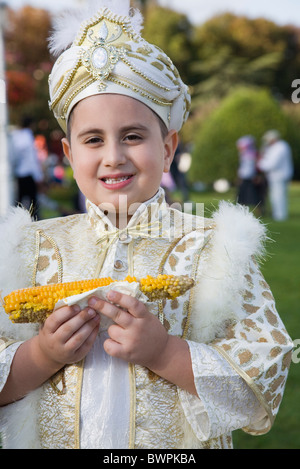 TURKEY Istanbul Sultanahmet Young boy eating sweetcorn cooked on the cob, wearing traditional Turkish ceremonial - Stock Photo