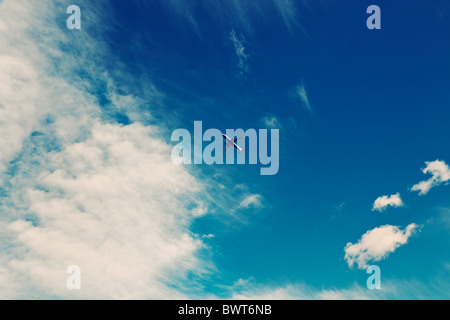Commercial airliner in cloudy sky - Stock Photo