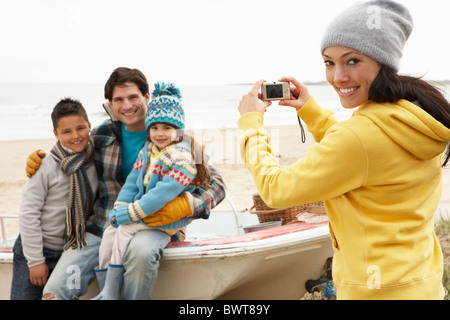 Mother Taking Family Photograph On Winter Beach - Stock Photo
