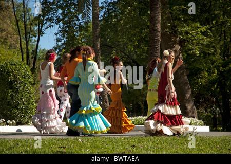 Women in flamenco dress walking through Maria Luisa Park towards the Seville Spring Fair, Seville, Andalusia, Spain. - Stock Photo