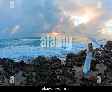 Young woman holding umbrella standing on rocks near ocean - Stock Photo