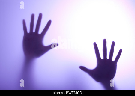 blurry hands reaching out and touching glass with Blue light - Stockfoto