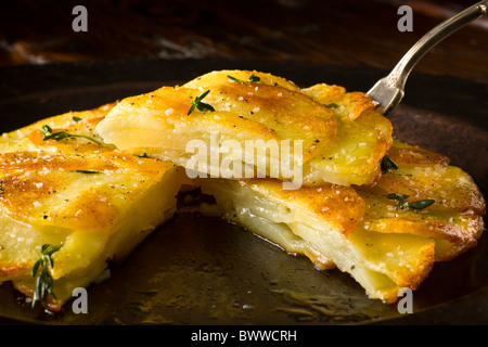 Potato Galettes or Anna garnished with fresh thyme, salt and pepper and served on a rustic plate. - Stock Photo