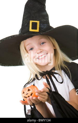 Portrait of girl in witch costume and small pumpkin in hands looking at camera - Stock Photo