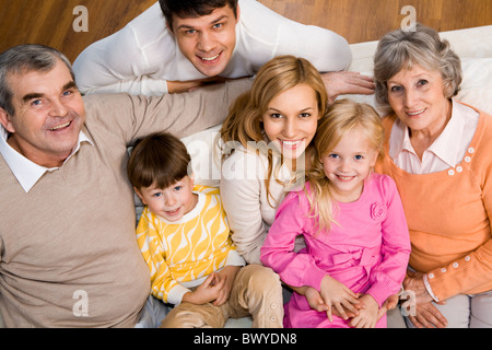 Above shot of senior and young couples with two children sitting on sofa and looking at camera - Stock Photo