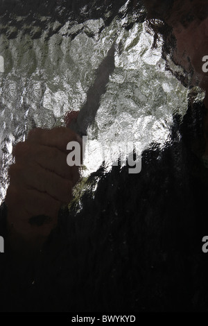 Silhouette of a male holding a knife, viewed through an obscured glass window. - Stock Photo