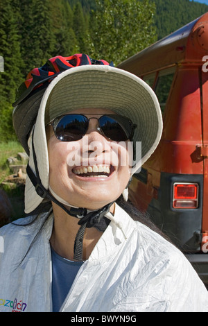 Woman wearing bicycle helmet over floppy sun hat prepares to ride the Hiawatha Trail in Idaho, USA. - Stock Photo