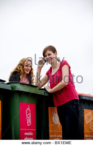 A teenage girl using a mobile phone in a recycling center - Stock Photo