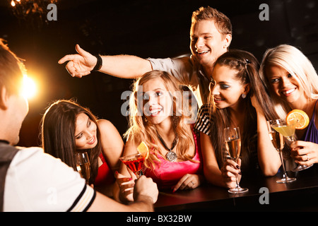 Photo of joyful friends in the bar communicating with barman - Stock Photo