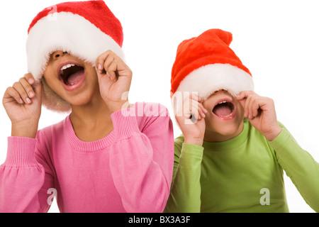 Photo of happy friends in Santa caps having fun over white background - Stock Photo