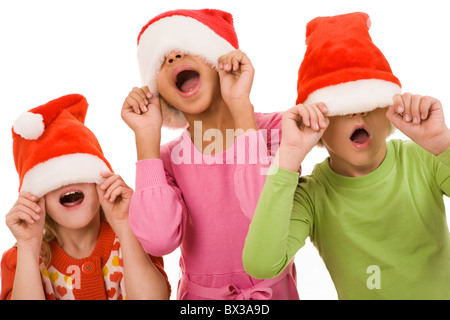 Photo of happy friends in Santa caps having fun together - Stock Photo