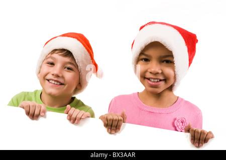 Photo of happy friends in Santa caps smiling at camera - Stock Photo