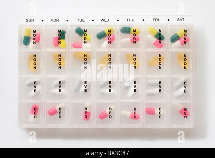 Different types of pills in a weekly dosage container - Stock Photo