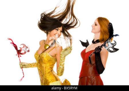 Photo of joyful actresses in fashionable dresses having fun over white background - Stock Photo