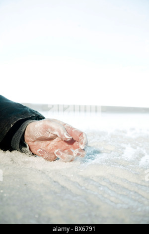 frozen hand lying on snow and ice. exterior location, - Stock Photo