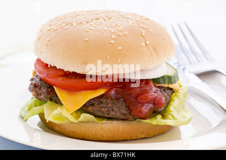 American cheeseburger stuffed with beef patty und cheddar as closeup on white background - Stock Photo