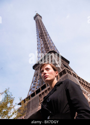 Woman stands in front of Eiffel tower - Stock Photo