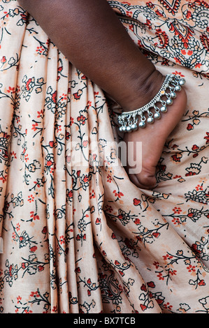 Indian babies foot against mothers patterned sari - Stock Photo
