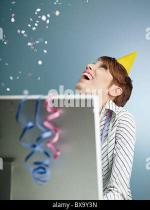 caucasian woman looking at confetti being thrown in office. Vertical shape, side view, waist up, copy space - Stock Photo