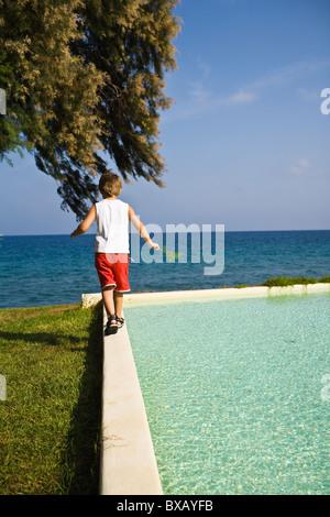 Boy walking on edge of pool - Stockfoto