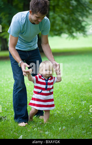 Mid adult father helping daughter with first steps - Stock Photo