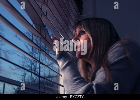 Worried woman looking out of a window blind at night. - Stockfoto