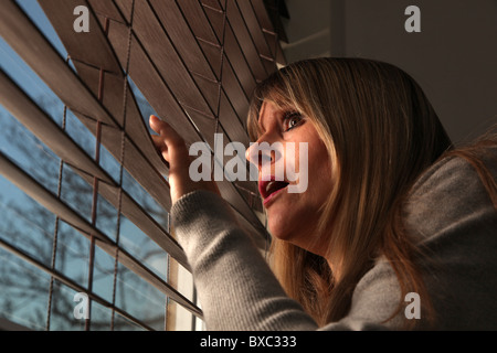 Middle aged woman with fair hair looking out of a window blind - Stockfoto