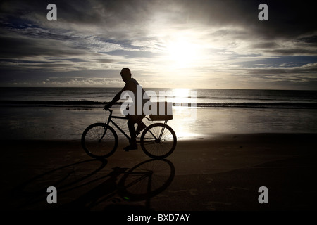 A male rides his bike to work at the beach at sunrise. - Stock Photo