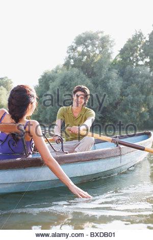 Man rowing girlfriend in rowboat on lake - Stockfoto