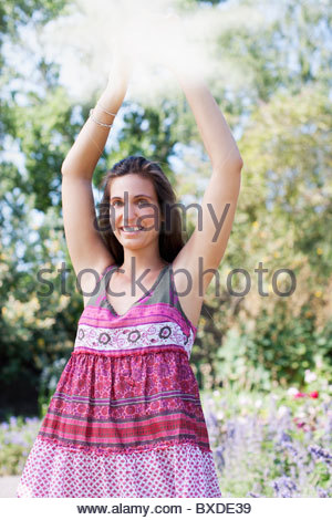 Smiling woman holding mirror in park - Stock Photo