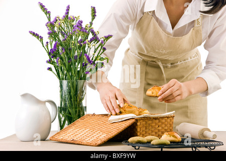 Young woman holding biscuit, close-up, mid section - Stock Photo