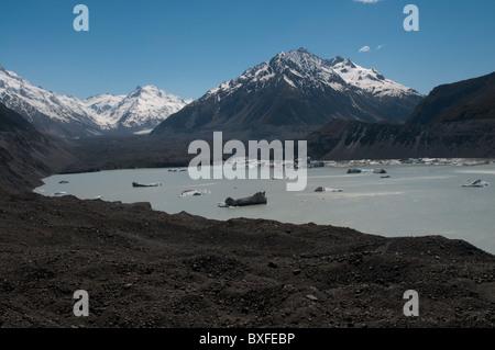 Hidden under dark debris the Tasman glacier is running down from Mount Tasman to the Tasman lake. - Stock Photo